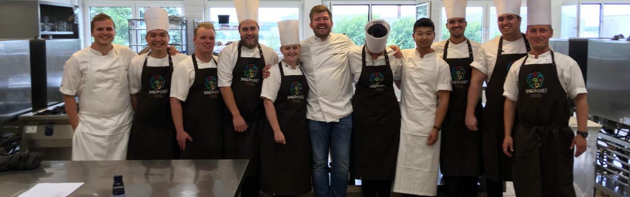 Kenneth Toft-Hansen og Christian Wellendorf i køkkenet med et hold kokkeelever på TechCollege. Foto: Simon Sørensen