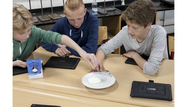 Eleverne har fremstillet deres egen ost i fysiktimen og smager den nu til med salt. Foto: Stagbird